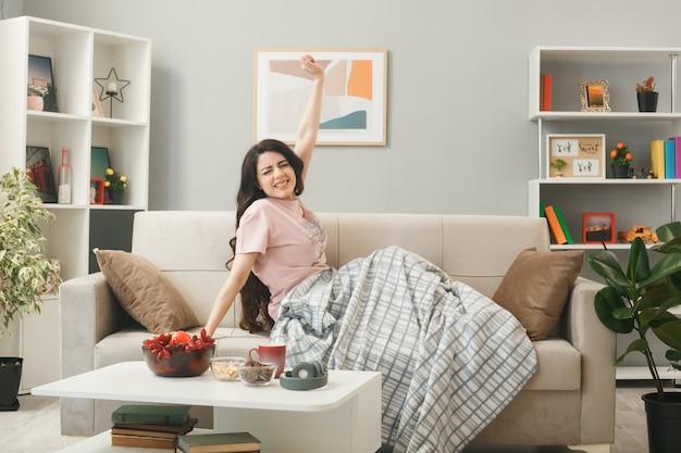 Jeune fille étirant le bras enveloppé dans un plaid assis sur un canapé derrière une table basse dans le salon