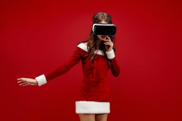 Jeune fille étonnée du père noël en robe de noël regardant dans un casque pointant les mains de côté isolées sur fond rouge...