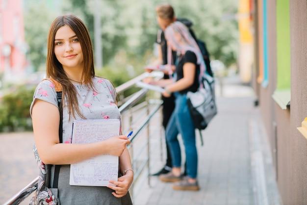 Jeune fille avec des études sur le porche de l'université