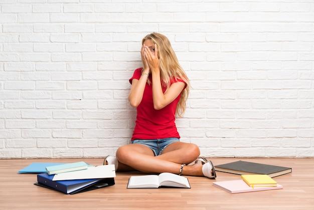Jeune fille étudiante blonde avec beaucoup de livres sur le sol, couvrant les yeux et regardant à travers les doigts