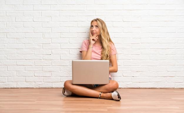 Jeune fille étudiante blonde avec un ordinateur portable sur le sol, pensant à une idée