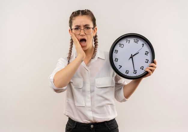Jeune fille étudiante dans des verres avec des nattes en chemise blanche tenant horloge murale à l'avant confus et très anxieux debout sur un mur blanc
