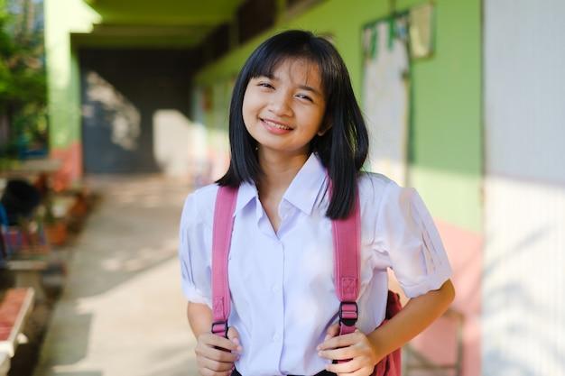 Jeune fille étudiante à l'école avec sac à dos rose