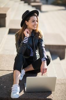 Jeune fille étudiante femme d'affaires travaille avec son ordinateur portable de marque dans le centre-ville