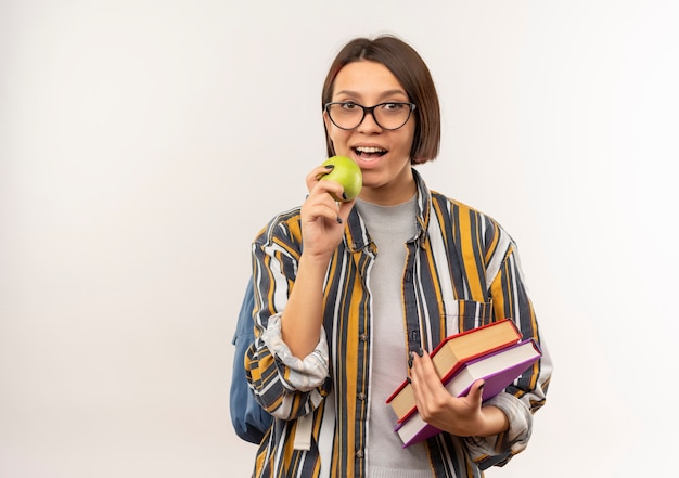 Jeune fille étudiante portant des lunettes et sac à dos tenant des livres et s'apprête à mordre apple isolé sur fond blanc avec espace copie