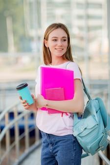 Jeune fille étudiante avec une tasse de café dans la rue