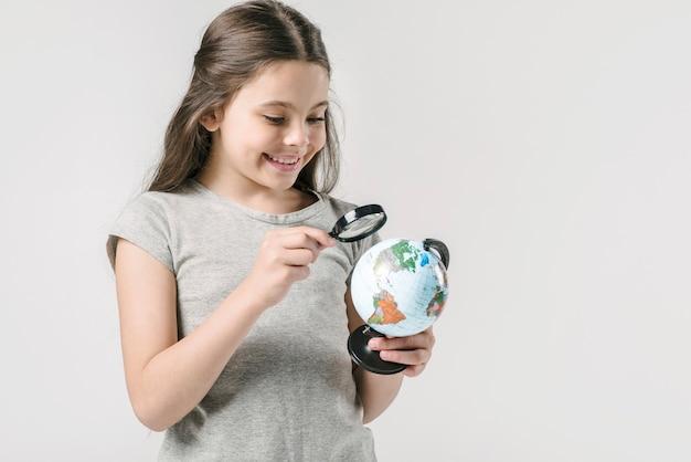 Jeune fille étudie globe avec loupe