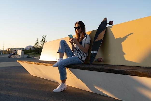 Jeune fille européenne chat à l'aide de l'application smartphone assis avec skate longboard dans le parc au coucher du soleil