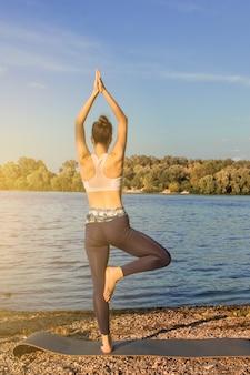 Une jeune fille européenne dans un survêtement léger pratique le yoga sur la rive du fleuve sur un tapis de yoga en caoutchouc