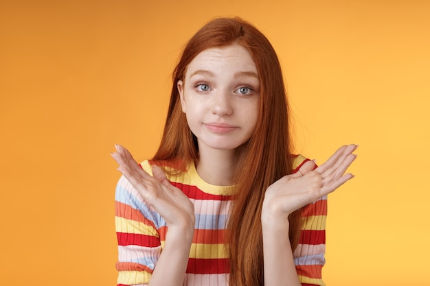 Une jeune fille européenne idiote rousse sans aucune idée des années 20, haussant les mains, se propage sur le côté avec un sourire narquois désolé ne peut pas répondre debout, inconscient, confus, perplexe, donne une réponse, fond orange.