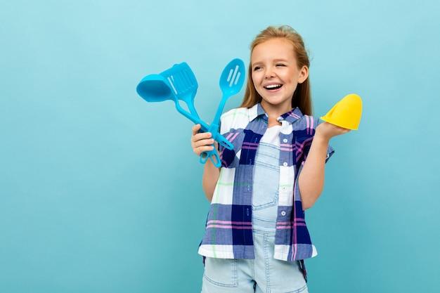 Jeune fille européenne souriante avec des ustensiles de cuisine en mains sur bleu clair