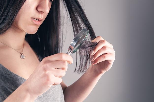 Une jeune fille examine ses cheveux avec une loupe. concept de problème de cheveux sur gris