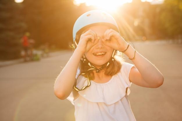 Jeune fille excitée en casque de patin à roues alignées en riant à la caméra à l'aide de jumelles à main imaginaire