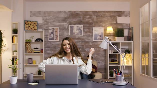 Jeune fille excitée devant un ordinateur portable tout en travaillant dans le salon. prise de vue au ralenti