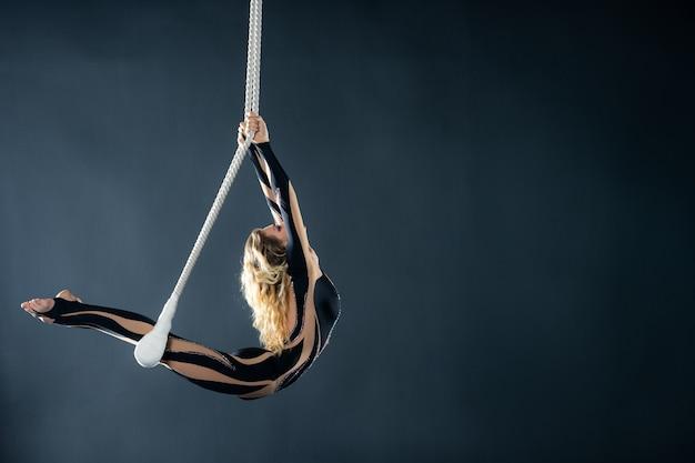 Une jeune fille exécute les éléments acrobatiques dans le trapèze aérien