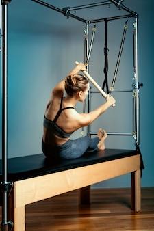 Jeune fille exerce sur un lit de réformateurs pilates, dans la salle sur un fond de mur gris.