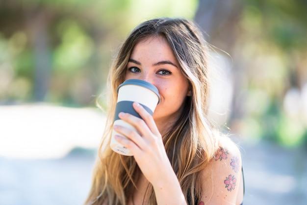 Jeune fille à l'extérieur dans un parc, tenant un café à emporter
