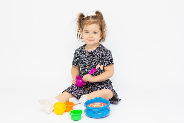 Jeune fille faire semblant de jouer la préparation de la nourriture dans le fond blanc