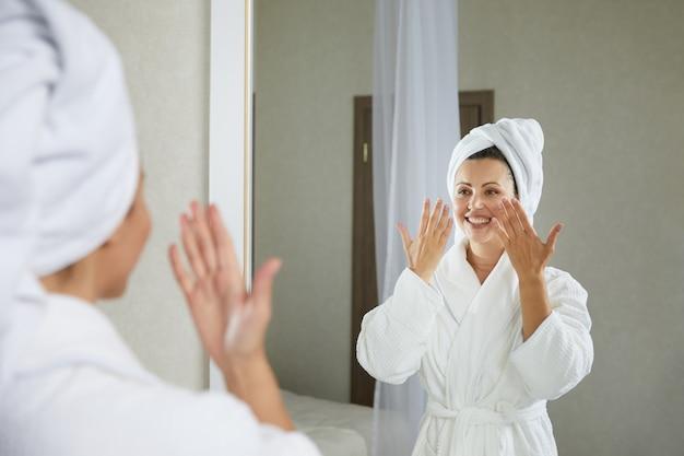 Jeune fille faisant de l'auto-massage de gymnastique faciale et des exercices de rajeunissement le matin après
