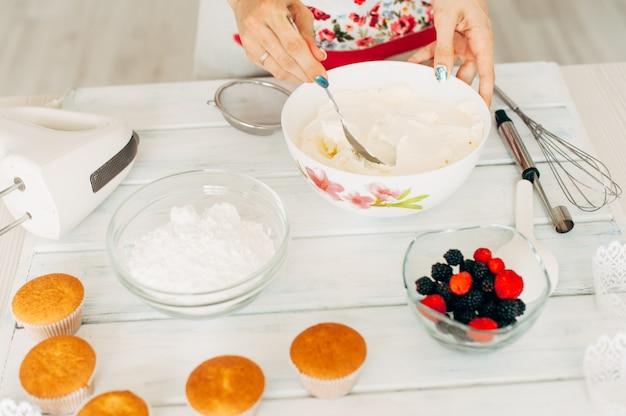 Jeune fille faisant de la crème pour les petits gâteaux.