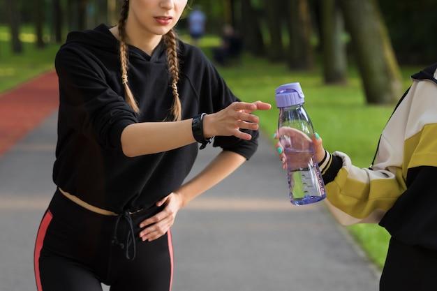 Une jeune fille, en faisant du jogging dans un parc, est tombée malade, elle boit de l'eau.