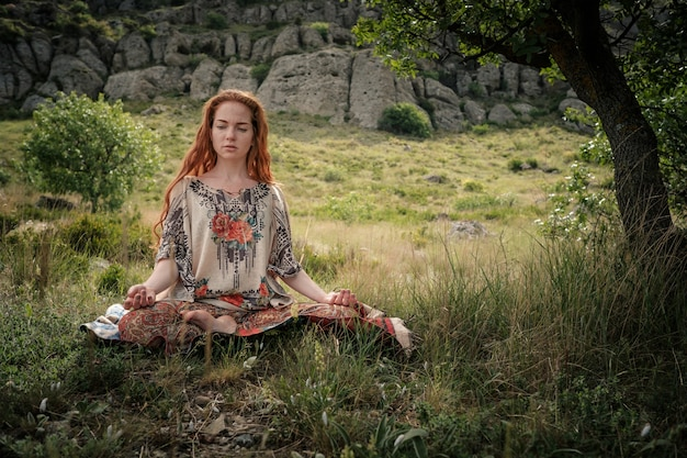 Jeune fille faisant du yoga dans le parc. calme et méditation. jeune fille rousse sous un arbre se détend