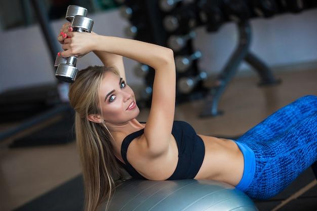 Jeune fille faisant de l'exercice sur le fitball avec des haltères