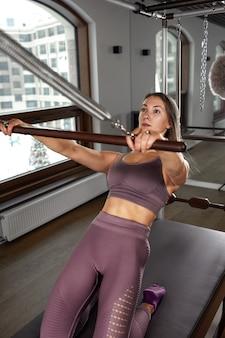 Jeune fille faisant des exercices de pilates avec un lit réformateur. bel entraîneur de fitness mince sur fond gris réformateur, discret, lumière d'art. notion de remise en forme.