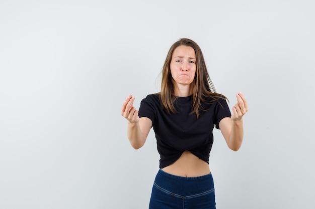 Jeune fille faisant des gestes avec les doigts en chemisier noir, pantalon et à la triste.