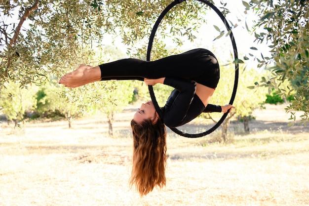 Jeune fille faisant une pose sur un cerceau aérien parmi les oliviers en été