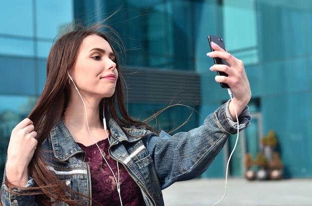 Jeune fille faisant selfie sur le fond d'un immeuble de bureaux
