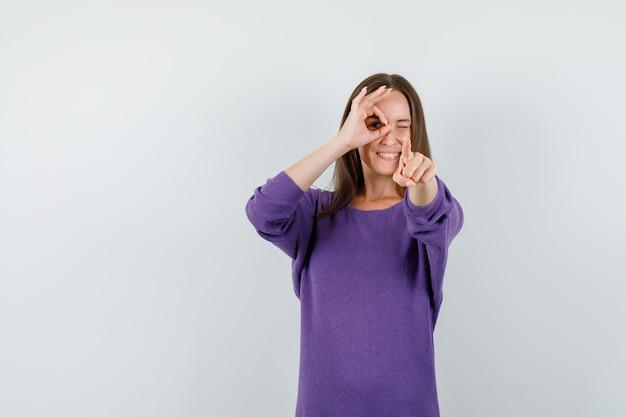 Jeune fille faisant signe ok sur les yeux et pointant la caméra en vue de face de chemise violette.