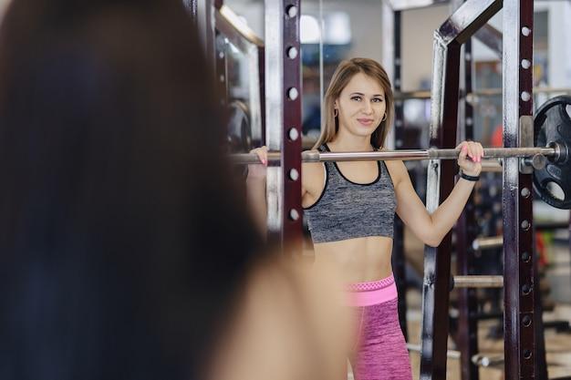 Jeune fille faisant des squats avec une barre dans la salle de sport