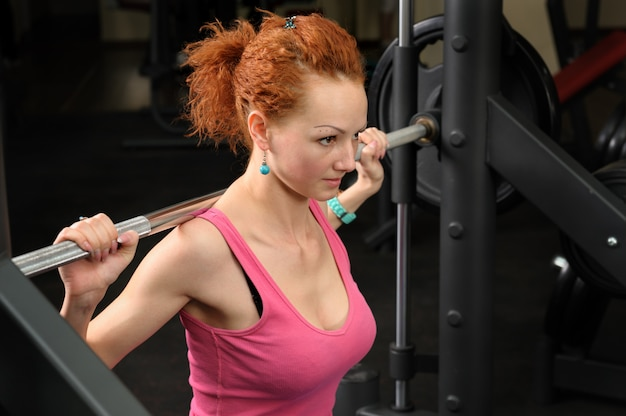 Jeune fille faisant des squats avec des haltères