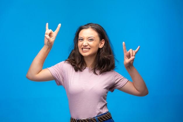 Jeune fille faisant le symbole de la paix avec les doigts et assez souriant.