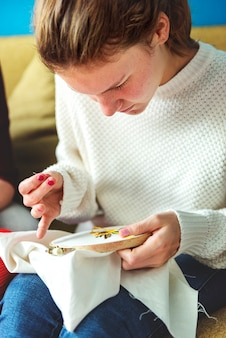 Jeune fille faisant des travaux d'aiguille