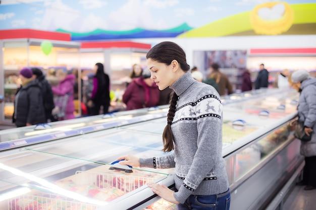 La jeune fille fait un achat à l'hypermarché d'épicerie