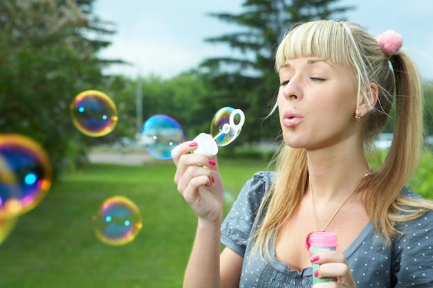 La jeune fille fait la bulle de savon sur l'herbe