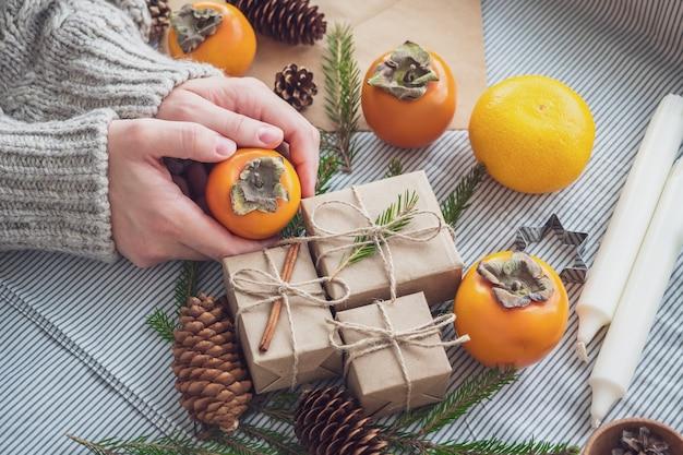 La jeune fille fait une composition de cadeaux du nouvel an emballé de ses propres mains dans du papier kraft, vue de dessus, gros plan. fond de noël joyeux. préparation des vacances. notion de noël.
