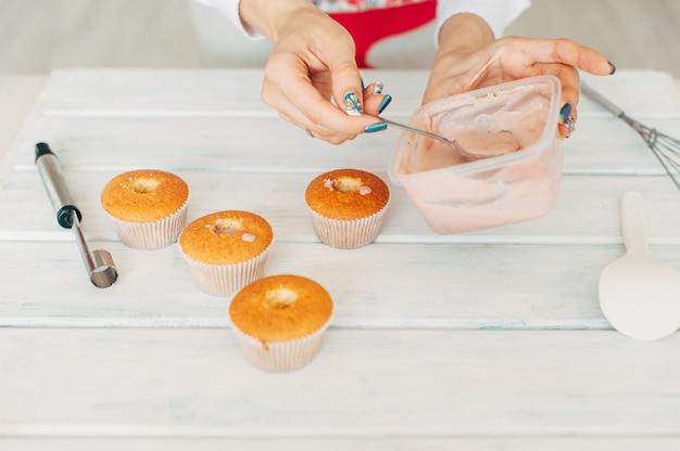 Jeune fille fait de délicieux cupcakes tendres.
