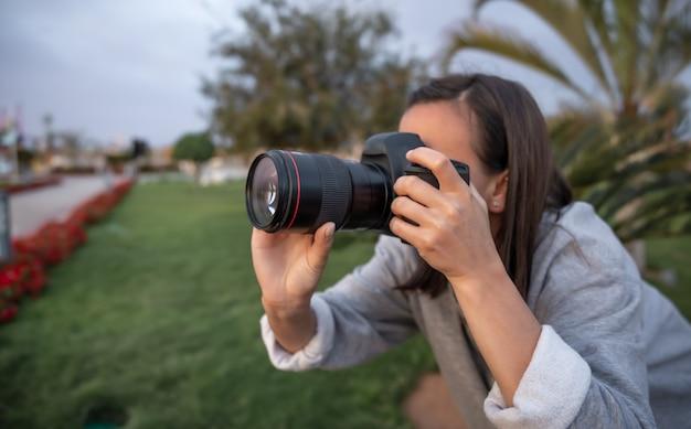 La Jeune Fille Fait Une Photo Sur Un Appareil Photo Reflex Professionnel à L'extérieur Dans La Nature De Près. Photo gratuit