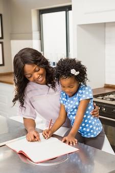 Jeune fille fait ses devoirs avec sa mère