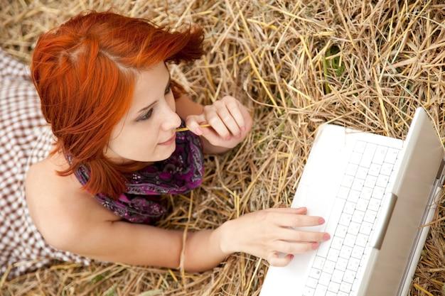 Jeune fille fashion avec carnet de notes se trouvant au champ