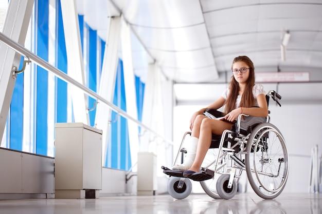 Une jeune fille en fauteuil roulant lit un livre. patient en fauteuil roulant dans le couloir de l'hôpital.