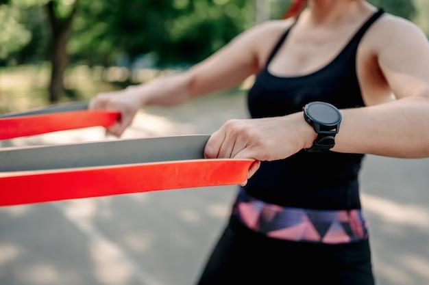 Jeune fille femme exerçant à l'extérieur avec une bande élastique en caoutchouc faisant de l'entraînement pour ses mains vêtu de s...