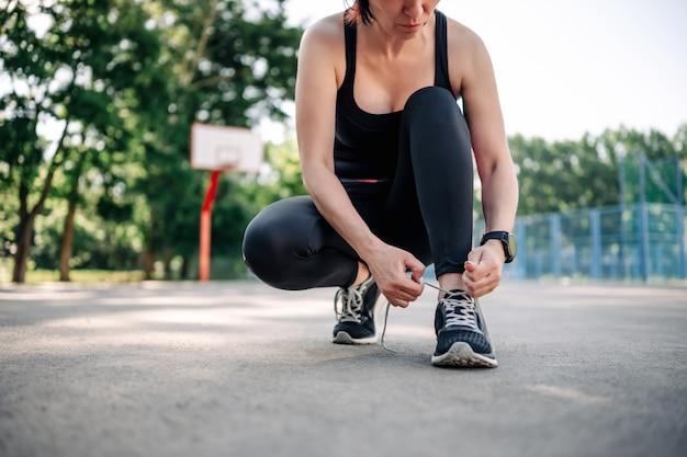 Jeune fille femme portant des vêtements de sport assis au stade et attachant des lacets se préparant à une activité d'entraînement...