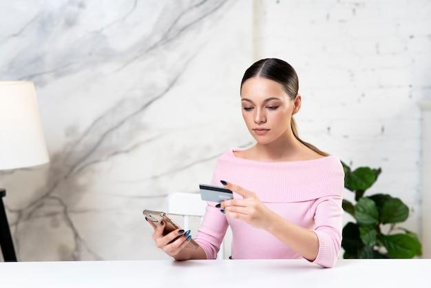 Jeune fille femme à la recherche de carte bancaire de crédit à payer en ligne dans la boutique à l'aide du service bancaire entrer