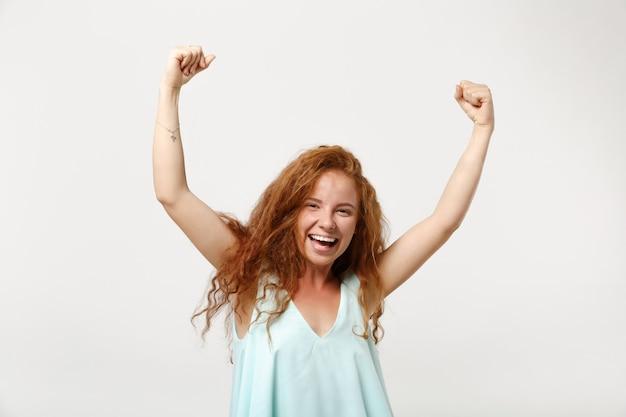 Jeune fille de femme rousse qui rit dans des vêtements légers décontractés posant isolé sur fond de mur blanc. concept de mode de vie des émotions sincères des gens. maquette de l'espace de copie. levant les mains, faisant le geste du gagnant.