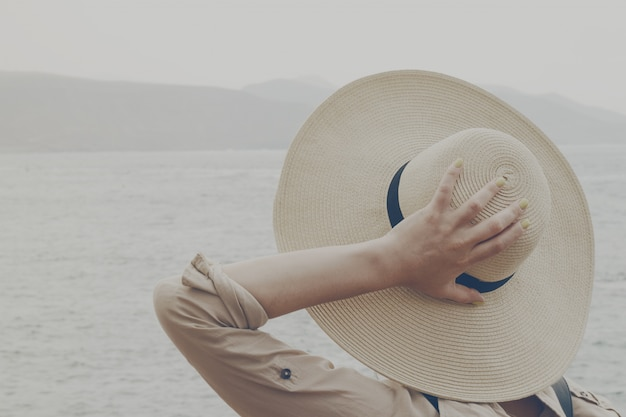 Jeune fille, femme tenant son chapeau de paille regardant sur l'océan. concept d'été de vacances de voyage. toning.