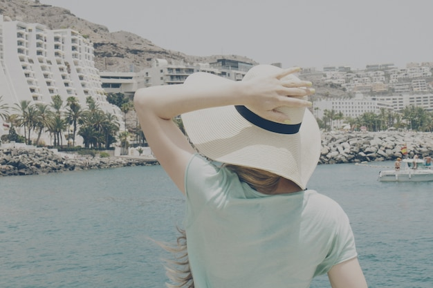 Jeune fille, femme tenant son chapeau de paille regardant sur l'océan et l'hôtel.